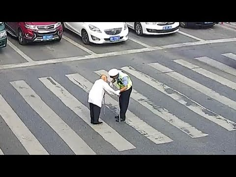 Watch: Traffic police helps elderly man cross the road by lifting him on his back!